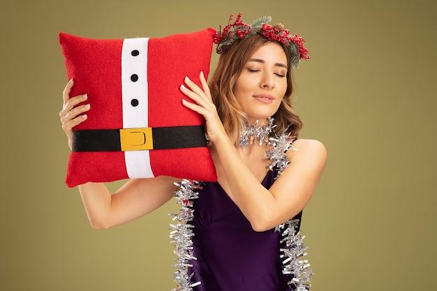 Zrelaksowana z zamkniętymi oczami młoda piękna dziewczyna ubrana w fioletową sukienkę i wieniec z girlandą na szyi, trzymająca świąteczną poduszkę odizolowaną na oliwkowym tle
