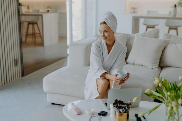 Zrelaksowana zamyślona kobieta ubrana w szlafrok i zawinięty ręcznik na głowie siedzi na sofie z filiżanką gorącej herbaty