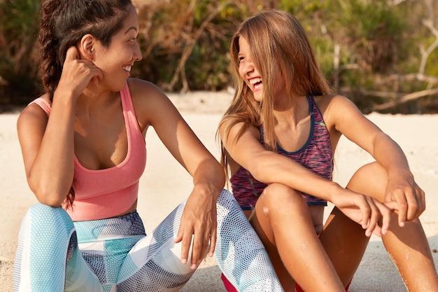 Zrelaksowane, szczęśliwe młode kobiety rasy mieszanej patrzą na siebie radośnie, cieszą się dobrym odpoczynkiem nad morzem lub wybrzeżem, ubrane w odzież sportową