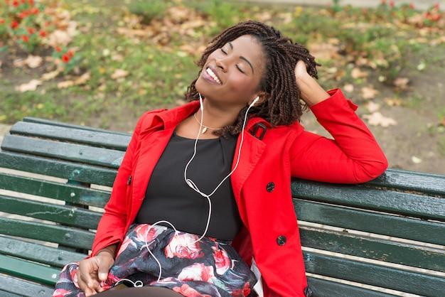 Zrelaksowanej kobiety słuchająca muzyka w parku