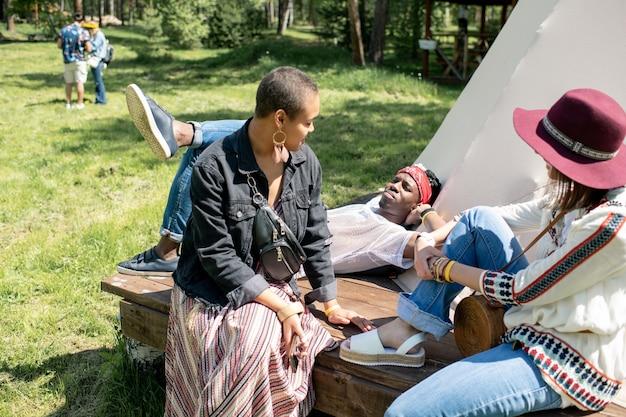 Zrelaksowani młodzi, wieloetniczni przyjaciele siedzą w namiocie i rozmawiają ze sobą, ciesząc się wypoczynkiem z dala od miasta