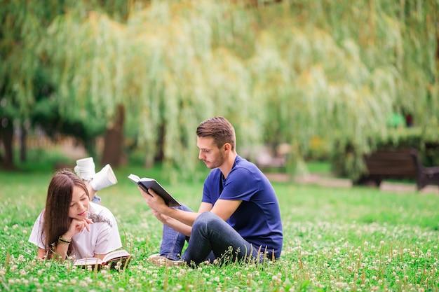 Zrelaksowani potomstwa dobierają się czytelnicze książki podczas gdy kłamający na trawie