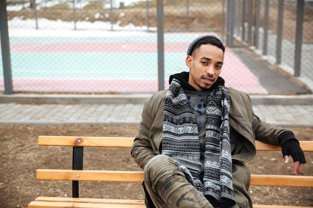 Zrelaksowany amerykanina afrykańskiego pochodzenia młodego człowieka obsiadanie i czekanie na ławce