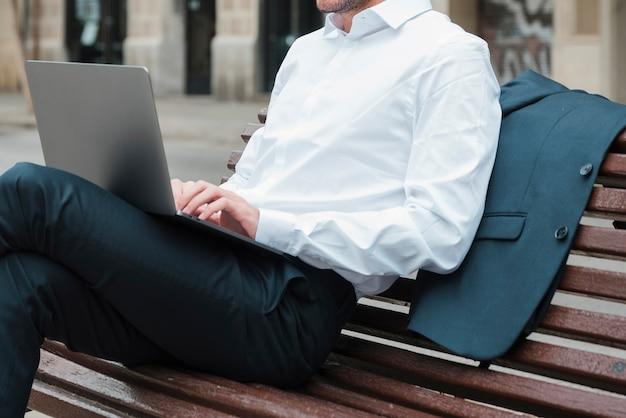 Zrelaksowany biznesmena obsiadanie na ławce używać laptop