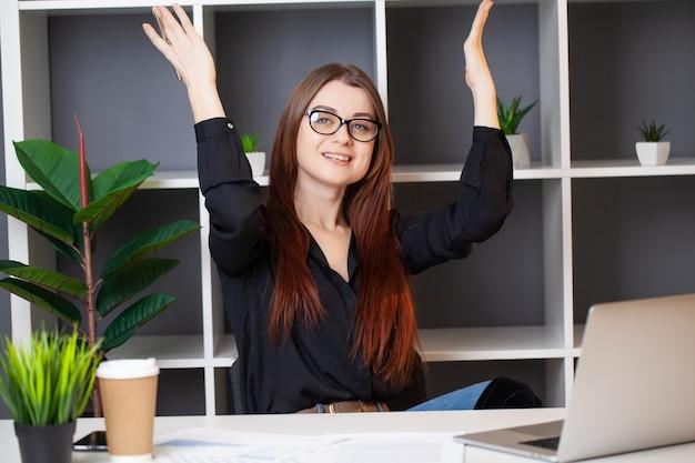 Zrelaksowany bizneswoman pracuje z laptopem w swoim biurze.