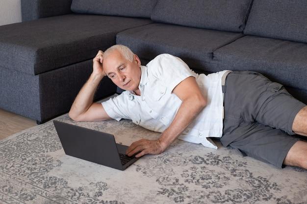 Zrelaksowany dojrzały mężczyzna pracujący w domu z laptopem, leżąc w pobliżu sofy