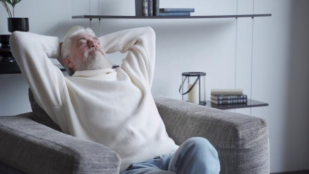 Zrelaksowany dojrzały mężczyzna z siwą brodą w domu siedzi na krześle