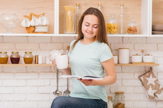Zrelaksowany domowy wypoczynek. kobieta pijąca herbatę i czytająca książkę w przytulnej kuchni