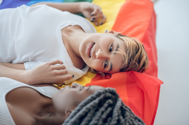 Zrelaksowany. dwie młode dziewczyny z tęczową flagą na podłodze
