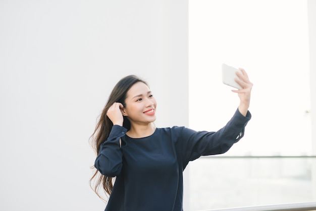 Zrelaksowany i wesoły. praca i wakacje. zewnątrz portret szczęśliwa młoda kobieta za pomocą smartfona, robi zdjęcie selfie i patrząc na ciebie na tarasie z pięknym widokiem na miasto.