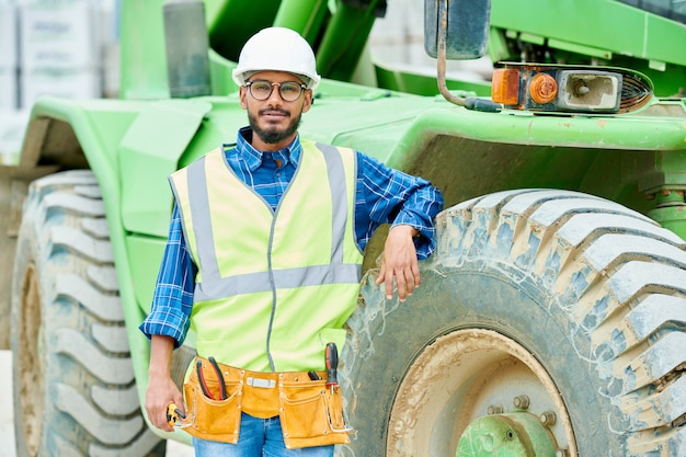 Zrelaksowany inżynier w pobliżu ciężkiej maszyny