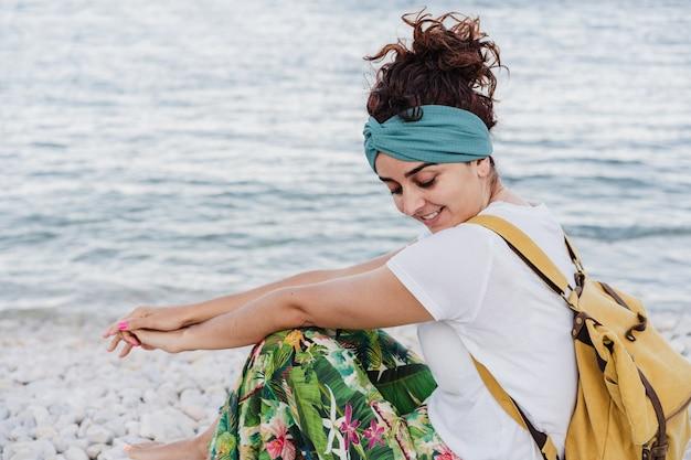 Zrelaksowany kaukaski kobieta siedzi przy plaży podczas zachodu słońca. noszenie żółtego plecaka.czas letni. marzyć. styl życia na zewnątrz