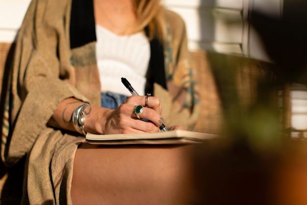 Zrelaksowany kobieta pisze w swoim dzienniku