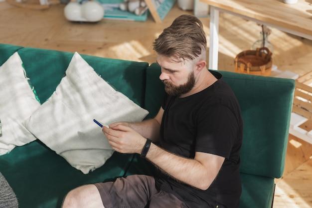 Zrelaksowany mężczyzna korzystający ze smartfona siedzący na zielonej kanapie w salonie w domu