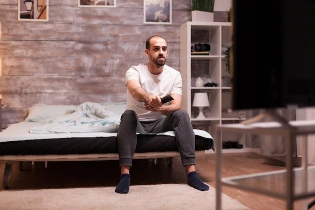 Zrelaksowany mężczyzna ogląda telewizję w nocy z krawędzi wygodnego łóżka.