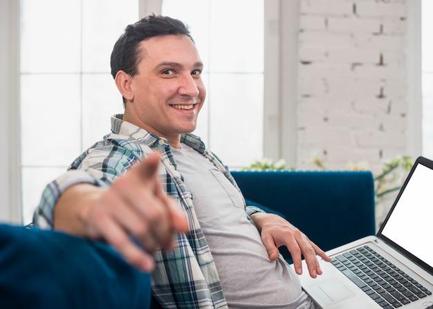 Zrelaksowany mężczyzna używa laptop w domu