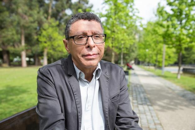 Zrelaksowany mężczyzna w średnim wieku siedzi na ławce w parku miejskim