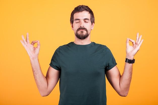 Zrelaksowany mężczyzna w stanie spokoju i spokoju z rękami na żółtym tle. zen, wellness w pozycji relaksacyjnej