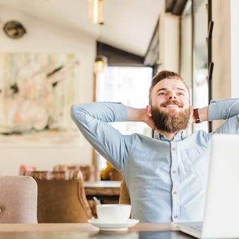 Zrelaksowany młodego człowieka obsiadanie w caf� z laptopem na biurku