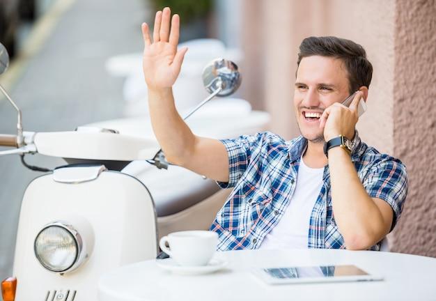Zrelaksowany młody człowiek rozmawia przez telefon i uśmiechnięty.