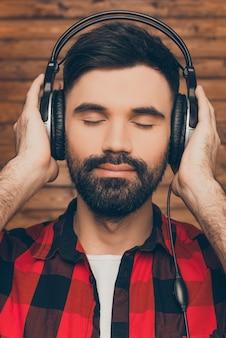 Zrelaksowany młody człowiek w słuchawkach słuchania muzyki z zamkniętymi oczami