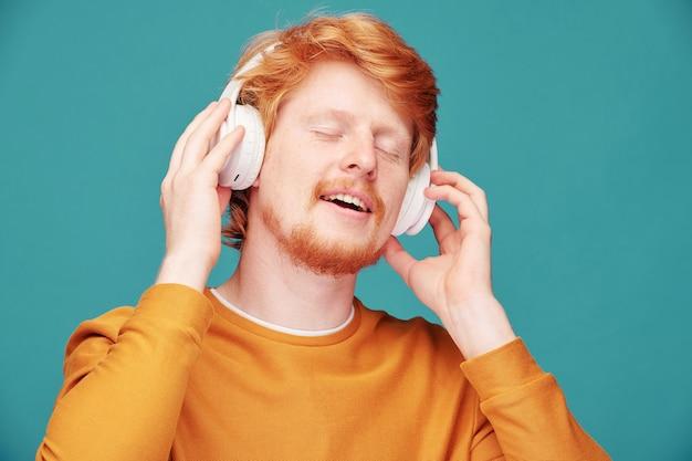 Zrelaksowany młody rudy mężczyzna w pomarańczowym swetrze z zamkniętymi oczami podczas słuchania muzyki w słuchawkach