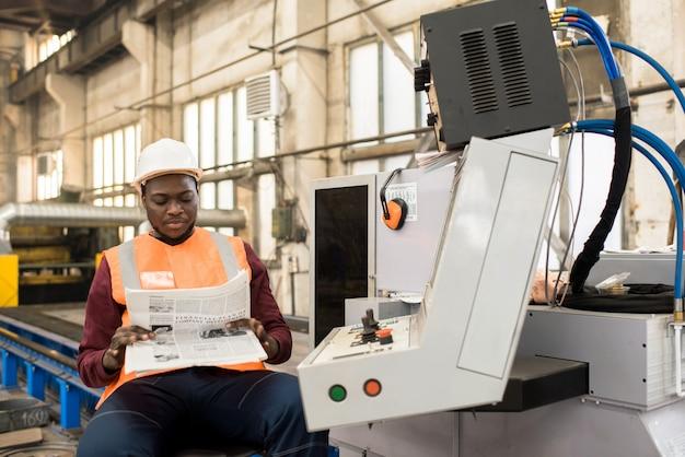 Zrelaksowany operator maszyny czytający gazetę