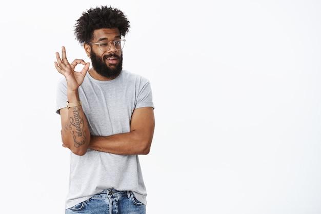 Zrelaksowany, pozytywny afroamerykanin mrugający z aprobatą i potwierdzający, pokazujący w porządku gest bez zmartwień, dający pozytywną opinię, zadowolony z doskonałego planu na szarej ścianie