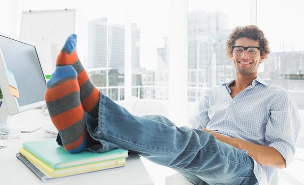 Zrelaksowany przypadkowy mężczyzna z nogami na biurku w biurze