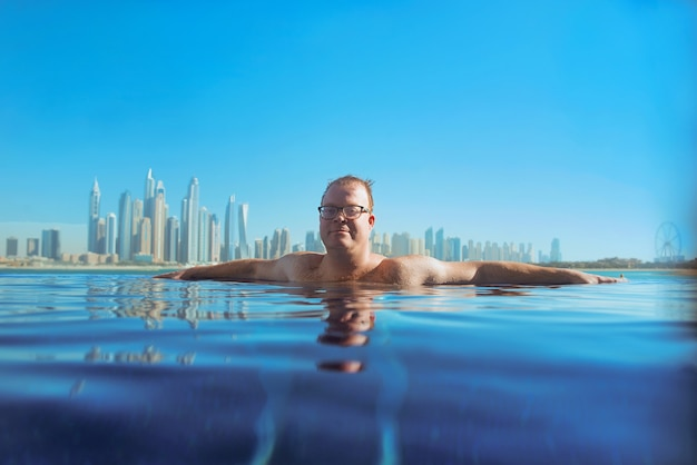 Zrelaksowany rudy mężczyzna z europy kaukaskiej na basenie w dubaju