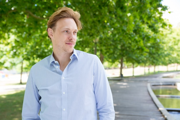 Zrelaksowany spokojny facet w pasiastej koszuli idąc przez park