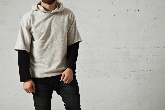 Zrelaksowany spokojny, wysportowany młody mężczyzna z brodą w czarnych dżinsach, czarnej koszulce z długim rękawem i zwykłej, szarej, wygodnej bluzie z kapturem na białym tle