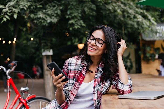 Zrelaksowany studentka siedzi na ulicy z laptopem i telefonem. urocza latynoska dziewczyna z czarnymi włosami pozuje w pobliżu jej roweru.