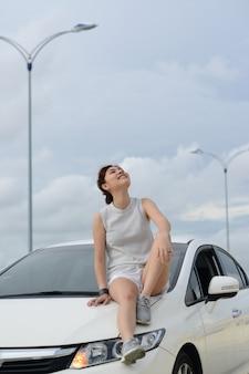 Zrelaksowany szczęśliwy drobna kobieta na wakacje. siedzieć w samochodzie. koncepcja stylu życia i ludzi.