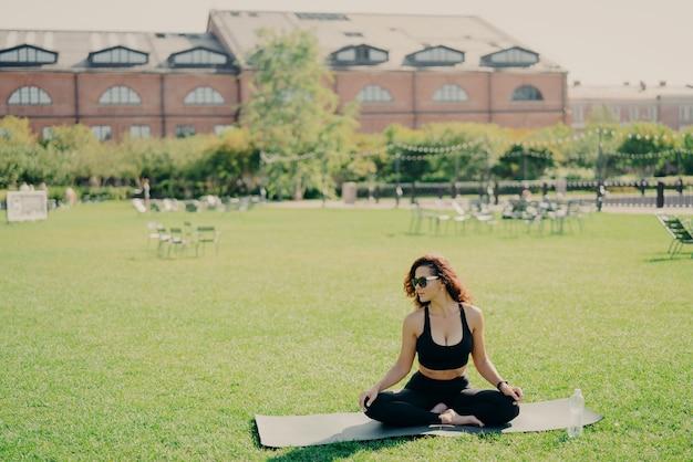 Zrelaksowany szczupła brunetka kaukaski kobieta siedzi w pozycji lotosu na macie fitness