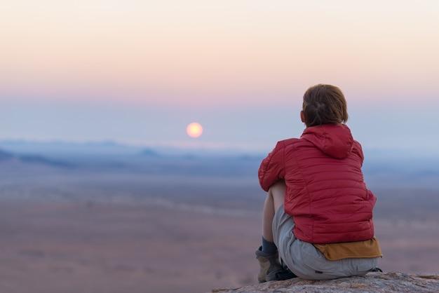 Zrelaksowany turysta siedzi na skałach i patrząc na zachód słońca