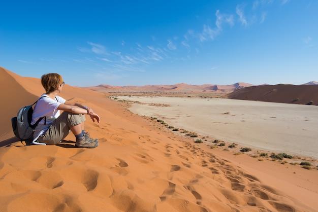 Zrelaksowany turysta siedzi na wydmach i patrząc na oszałamiający widok w sossusvlei, pustynia namib, namibia, afryka