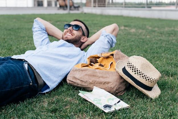 Zrelaksowany uśmiechnięty mężczyzna kłama na trawie z podróżnymi akcesoriami