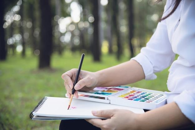 Zrelaksuj się kobieta, malowanie akwarelami dzieła sztuki w zielonym ogrodzie lasu natury