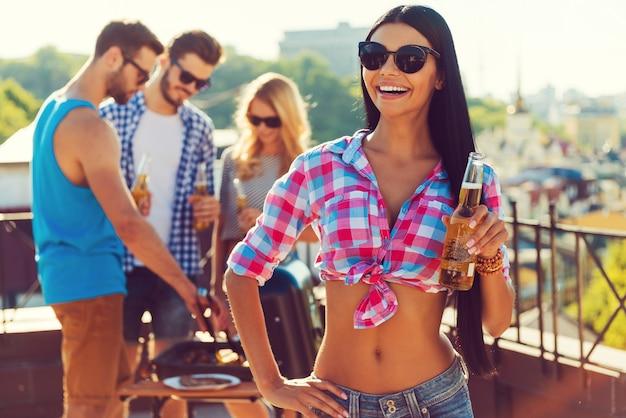 Zrelaksuj się z przyjaciółmi. szczęśliwa młoda kobieta trzyma butelkę z piwem i uśmiecha się, podczas gdy trzy osoby grillują w tle