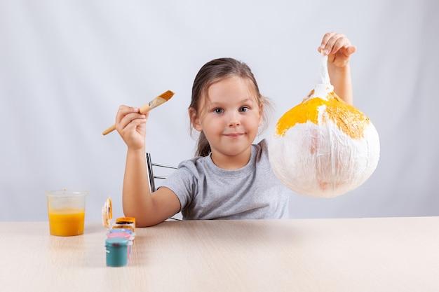 Zrób to sam na halloween, dziewczynka trzymająca dynię z papier-mache i serwetki.
