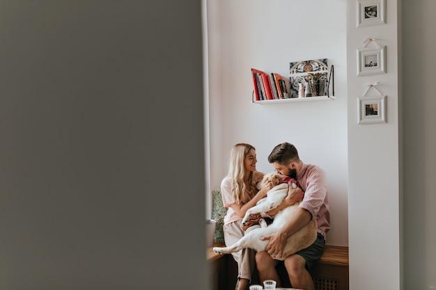 Zrób zdjęcie przez otwarte drzwi pary kochanków bawiących się z dużym białym psem w przytulnym, jasnym pokoju.