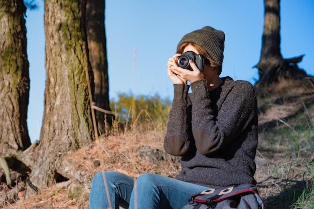 Zrobienie zdjęcia starym aparatem analogowym w lesie. kobieta turysta za pomocą aparatu w scenie pięknej przyrody w jasny słoneczny dzień