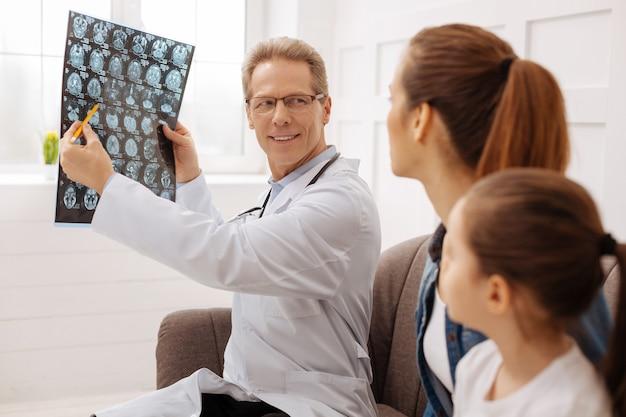 Zrobiłeś pewne postępy. doświadczony, uroczy, profesjonalny chirurg, który dzieli się miłymi informacjami z rodziną pacjentów, jednocześnie wskazując coś na zdjęciu rentgenowskim, które trzyma