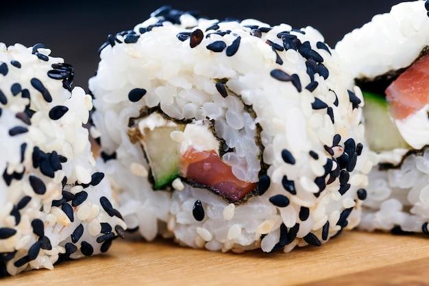 Zrobione z ryżu i pstrąga lub łososia z awokado sushi, azjatyckim ryżem i owocami morza na stole podczas posiłków, azjatyckimi rybami i produktami z awokado