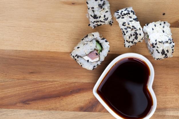 Zrobione z ryżu i pstrąga lub łososia z warzywami jedzenie sushi z sosem sojowym, azjatycki ryż i owoce morza na stole podczas posiłków, azjatyckie produkty spożywcze i sos sojowy