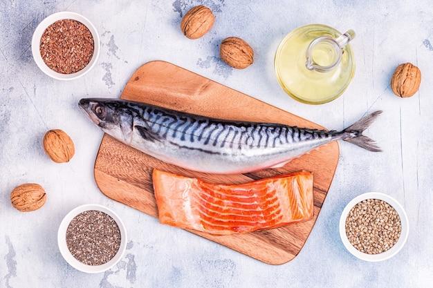 Źródła omega 3 - makrela, łosoś, siemię lniane, nasiona konopi, chia, orzechy włoskie, olej lniany. koncepcja zdrowego odżywiania. widok z góry z miejscem na kopię.