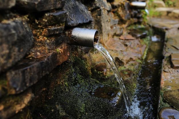 Źródlana woda wylewa się z metalowej rury z kamiennej ściany w lesie w górach.