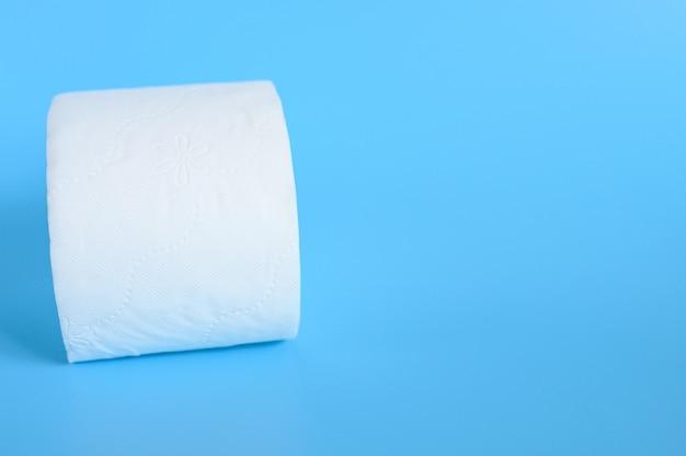 Zrolowany biały papier toaletowy na niebieskim tle. miejsce na tekst