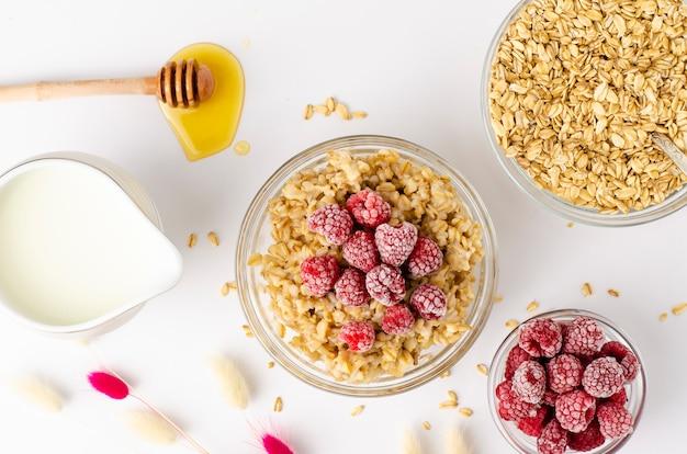 Zrównoważona dieta menu na śniadanie z miską owsianki owsianej z malinami i miodem
